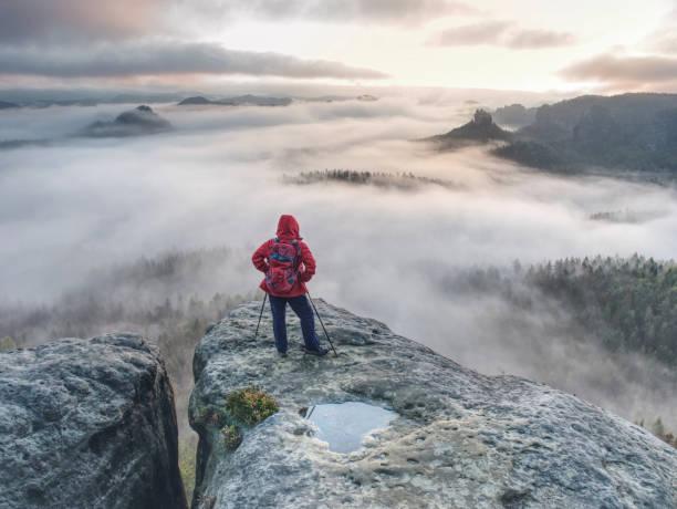 Backpacker stay on wet rock. Misty daybreak in rocky mountains stock photo