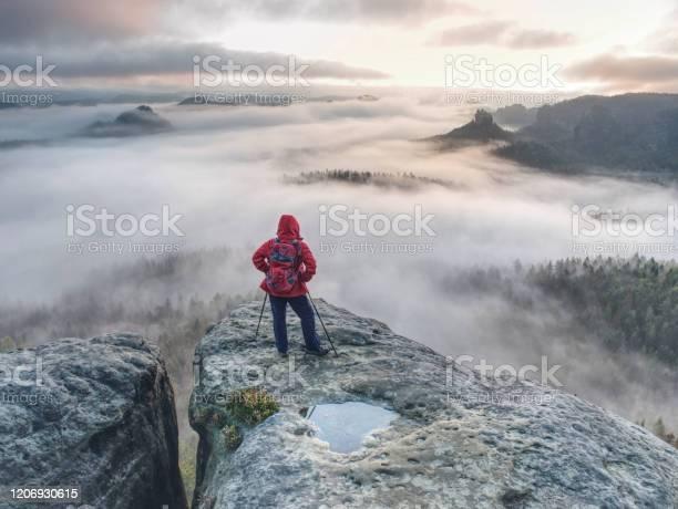 Photo of Backpacker stay on wet rock. Misty daybreak in rocky mountains