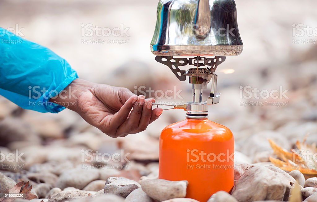 Backpacker tourist's hand regulating gas flame of camping stove. stock photo