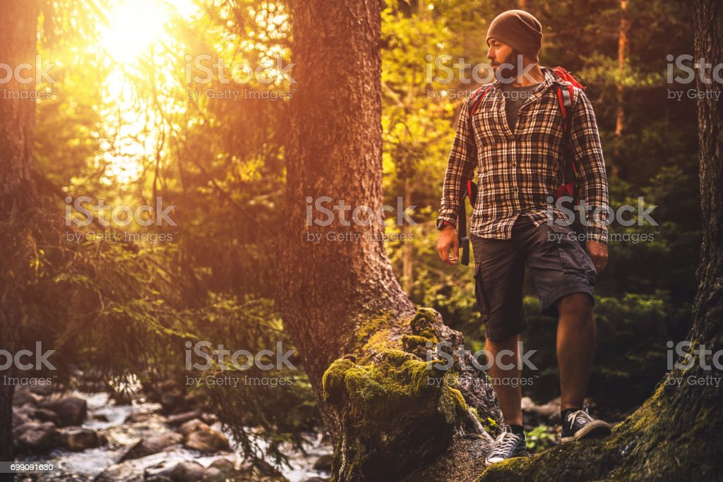 Backpacker trail hiking alone in the forest at sunset stock photo