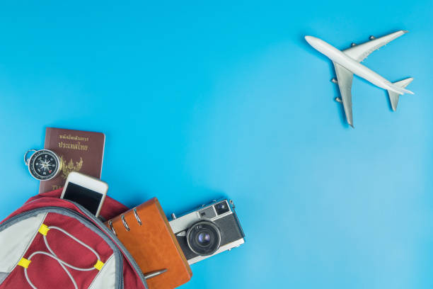 backpacker travel accessories with plane fly pass on blue - phone, travelling, copy space imagens e fotografias de stock