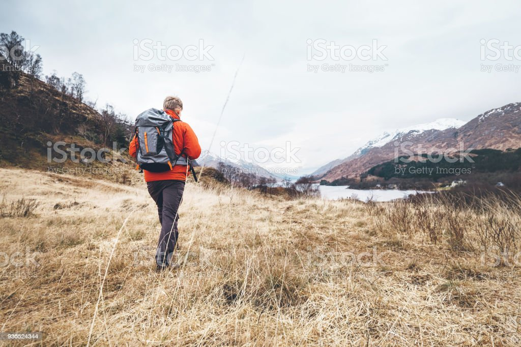Backpacker traveler walks among the hills stock photo