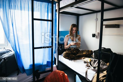 Backpacker using her phone in a hostel at Varanasi, India