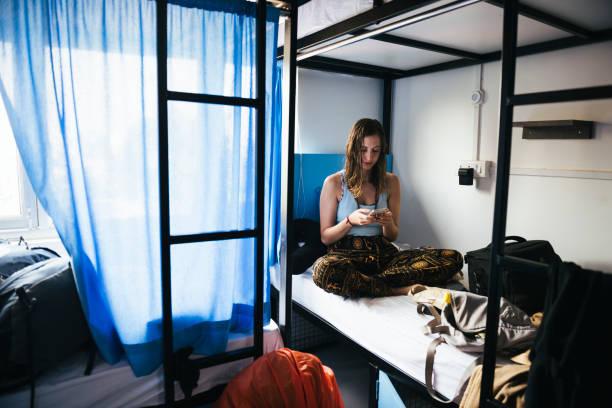 backpacker mit ihrem handy in einem hostel in varanasi, indien - etagenbett weiss stock-fotos und bilder
