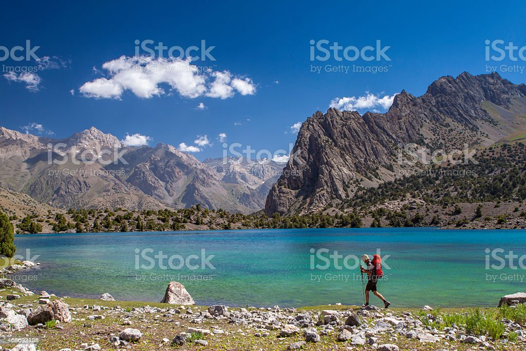 Backpacker walking along the turquoise water of the mountains lake. stock photo