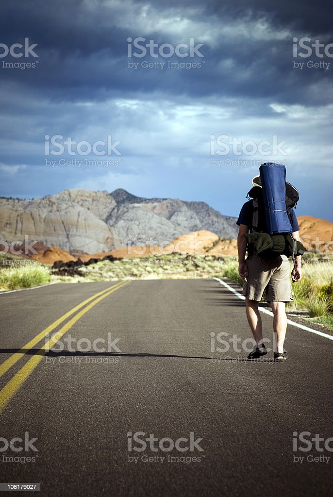 Backpacker walking down a road in southern Utah royalty-free stock photo
