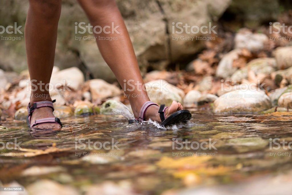 Backpacker walking in creek stream water. stock photo