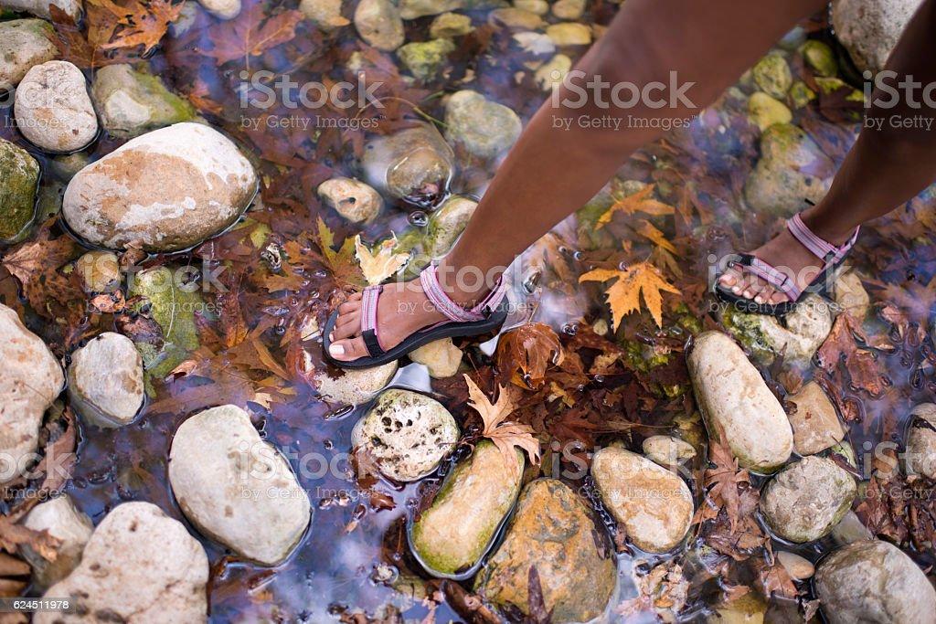 Backpacker walking in creek water. stock photo