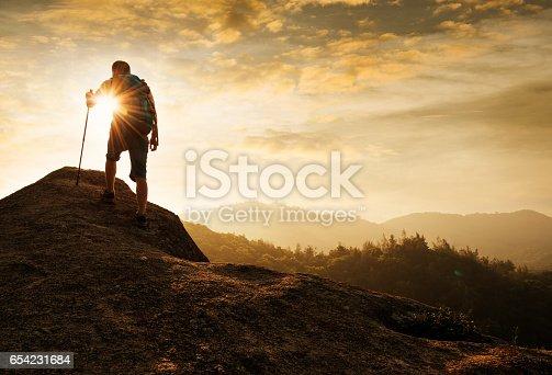 Male backpacker walking on mountain peak.