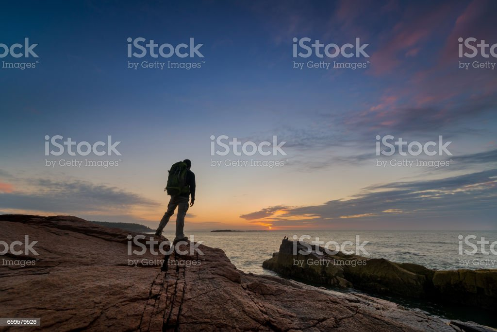 Backpacker watching the sunrise in Maine stock photo