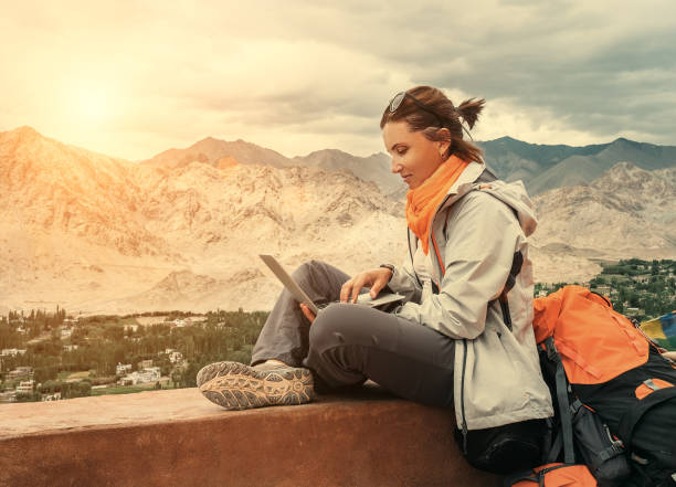 backpacker with laptop sits on the top view point under mountain settelment - reiseblogger stock-fotos und bilder