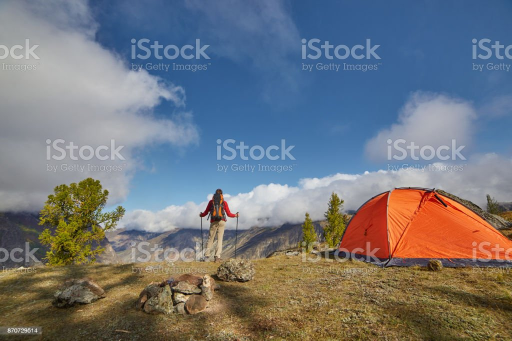 Backpacker with poles in hand. stock photo