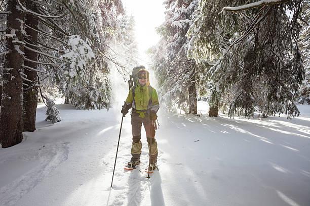 randonneur femme marchant dans la forêt d'hiver - raquette photos et images de collection