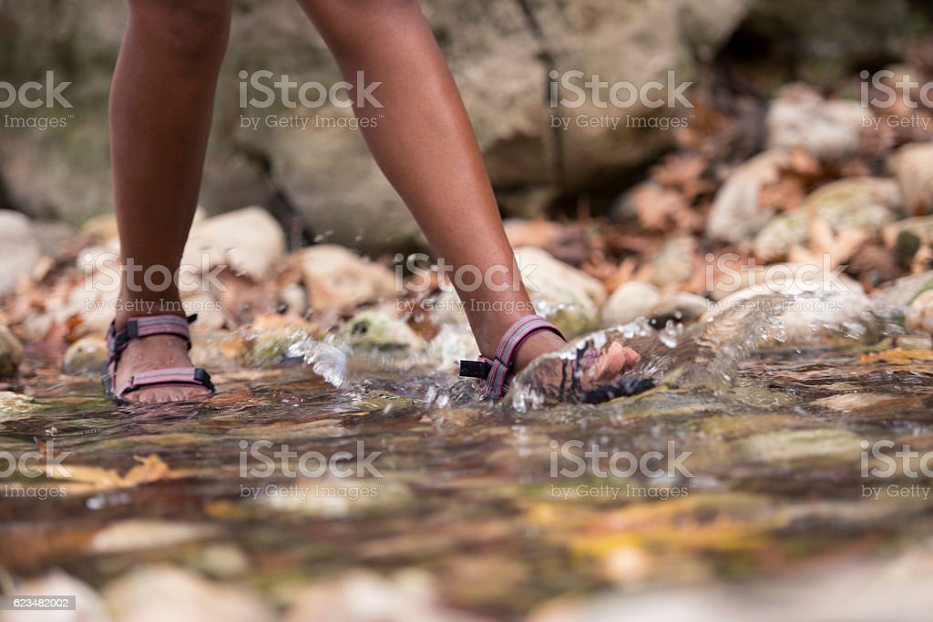 Backpacker woman's feet wading in brook. stock photo