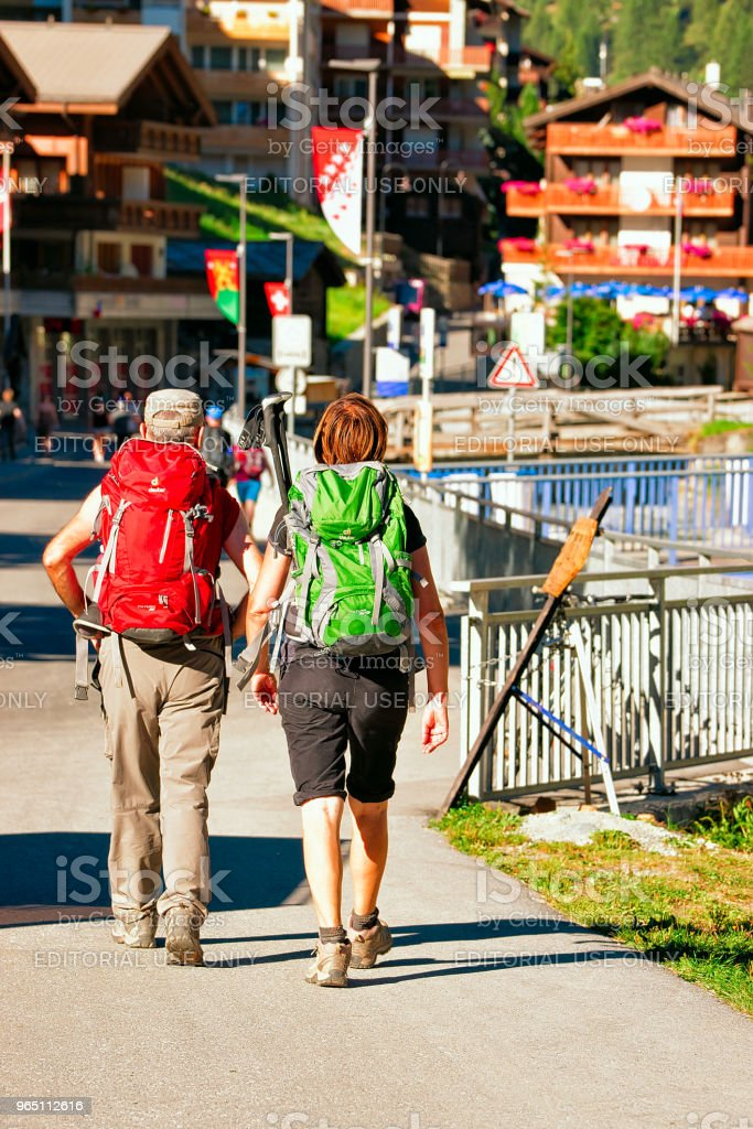 Backpackers at the street of resort city Zermatt in CH royalty-free stock photo