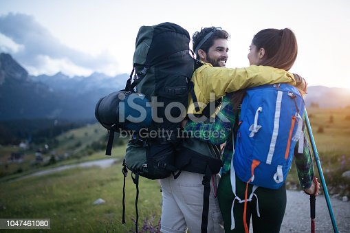 524621933 istock photo Backpackers couple hiking during fall with sticks 1047461080