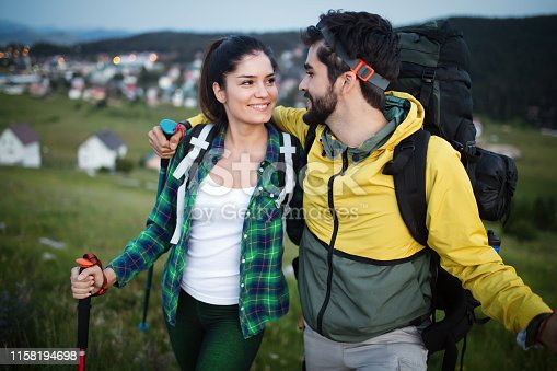 524621933 istock photo Backpackers couple hiking during fall with sticks 1158194698