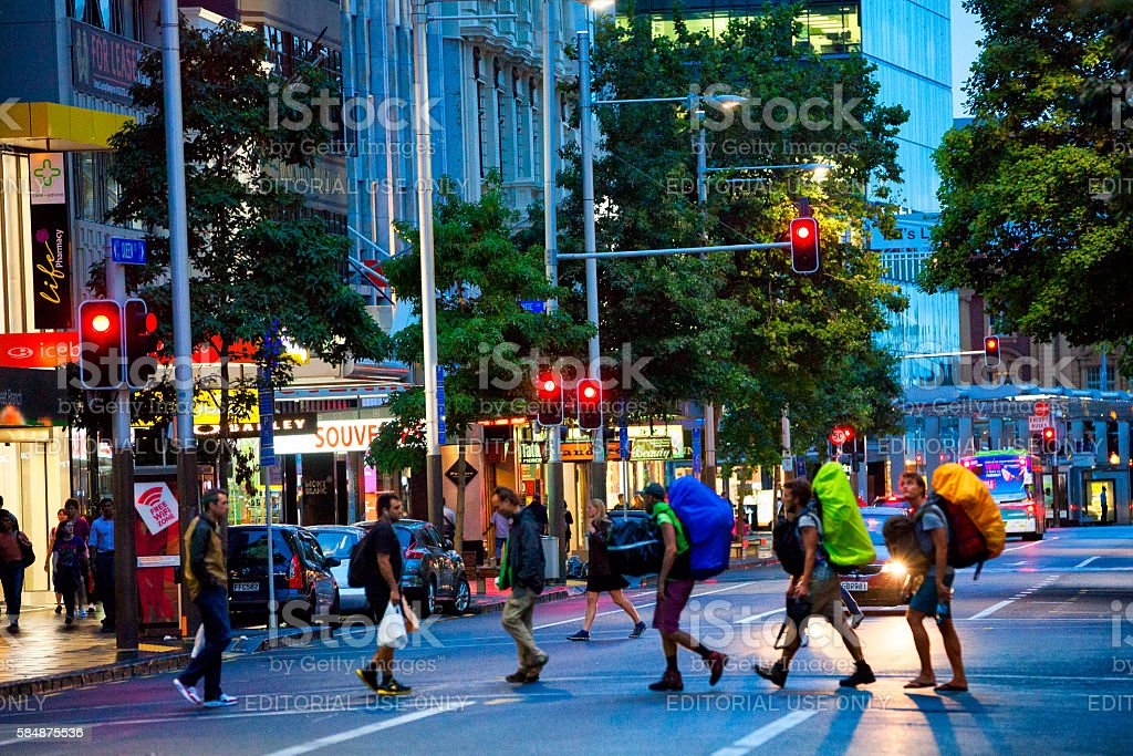 Backpackers crossing Queen street in downtown Auckland, New Zealand stock photo