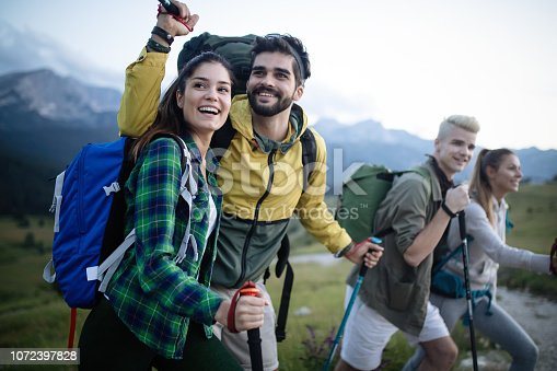 524621933 istock photo Backpackers happy young couple hiking with sticks 1072397828