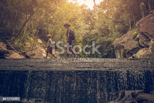 Woman and boy Backpacker hiking in rainforest