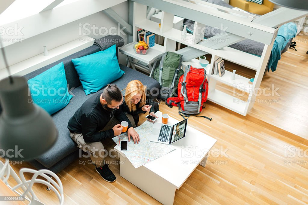Backpackers Looking At Map In Their Rented Apartment. stock photo