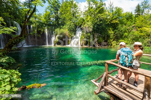 Tourists standing on a wooden platform and enjoying the view of the beautiful lake with the waterfalls. Plitvička Jezera, Croatia - June 25th 2019 - Official photography permission obtained by the Plitvice Lakes National Park and available on request.
