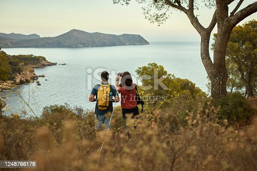 Rear view of Spanish couple in 20s and 30s pausing from hiking coastal trail to take picture of Mediterranean Sea.