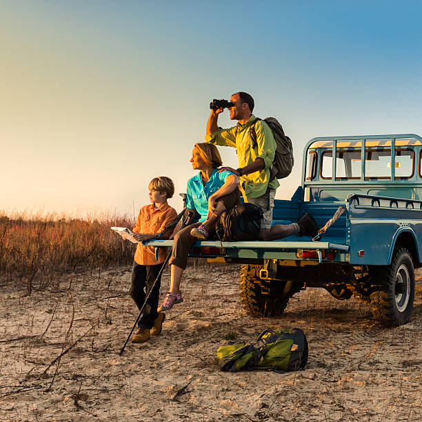 backpacking family on vehicle at sunset - safari stock photos and pictures