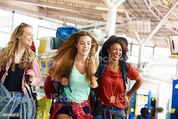 Three female backpacking friends make their way to depart for the next part of their journey. They are carrying their backpacks, checking the timetable and having a laugh.