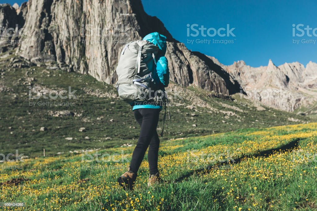 backpacking woman hiker walking on beautiful mountains stock photo
