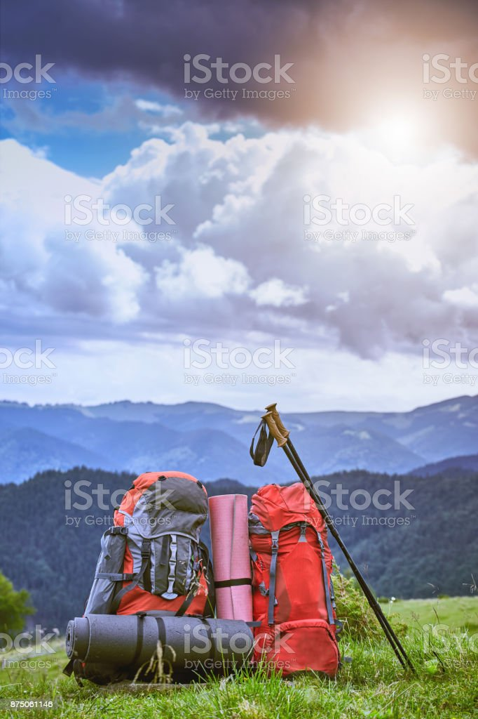 Backpacks in the mountains overlooking the mountains on the green grass. stock photo