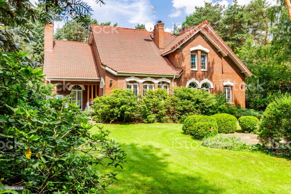 Backround yard of a beautiful english style house with bushes and green lawn. Real photo stock photo