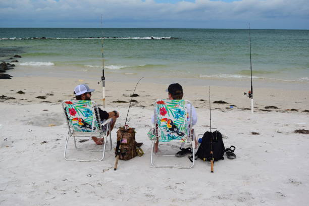 Backs of two men sitting and fishing at ocean stock photo
