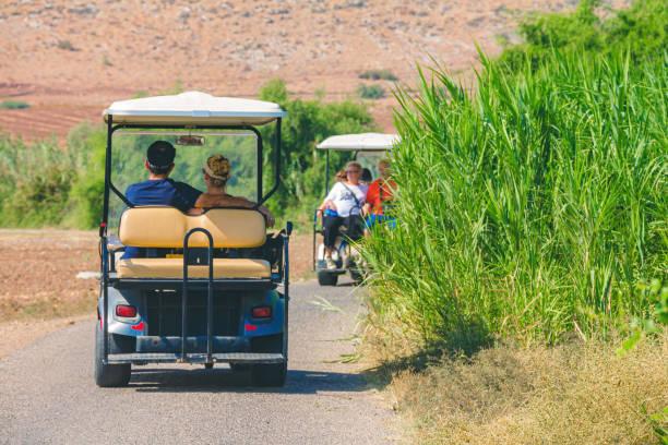 Backshot of Israeli people driving on electric golf cart stock photo