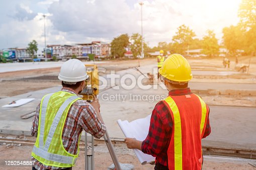 istock Backside engineer team working the surveyor at the construction site 1252548887