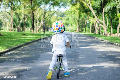 istock Backside of cute Asian 2 years toddler boy child wearing safety helmet learning to ride first balance bike 1060652838