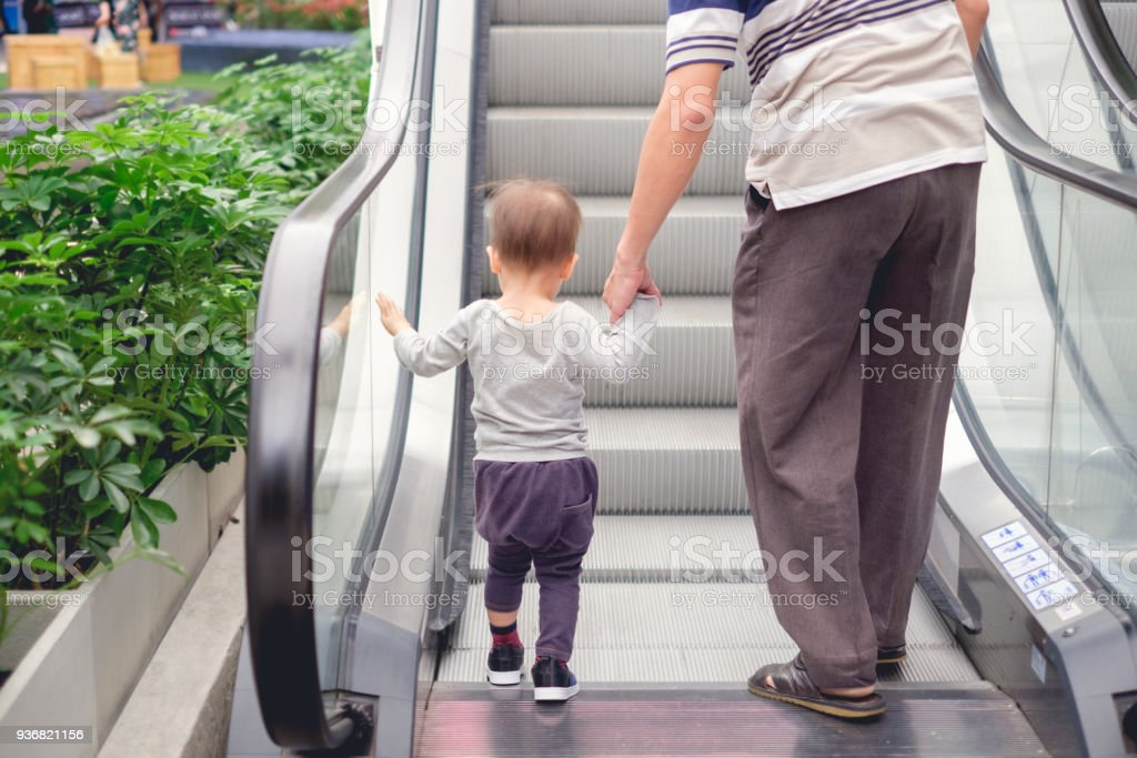 Backside of Cute little Asian 18 months / 1 year old toddler baby boy child and dad holding hands on moving escalator at department store stock photo