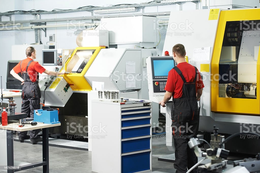 Backside of two employees working at a tool workshop stock photo