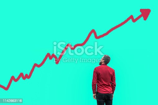 904389218istockphoto Backside of young bearded handsome businessman in red shirt standing and looking at growing graph chart analysis diagram drawed on copy space of blue background 1142663116