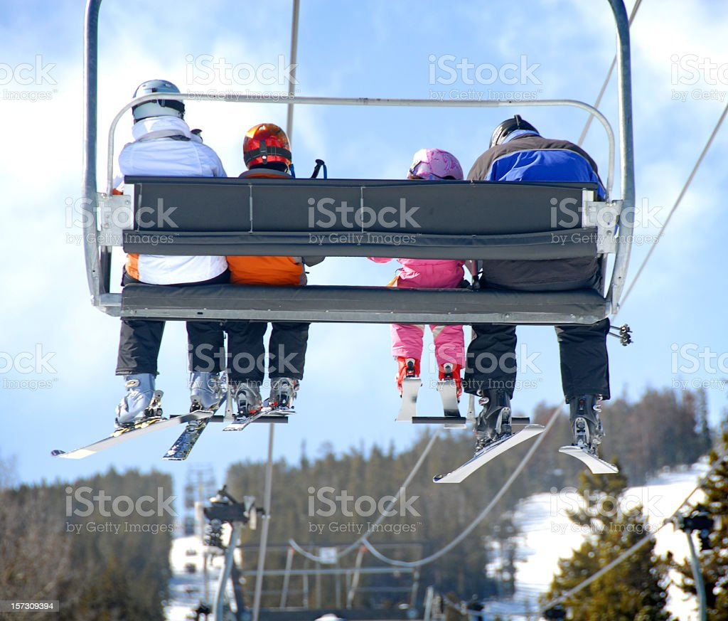 Backside view of a family on a ski vacation riding the lift stock photo