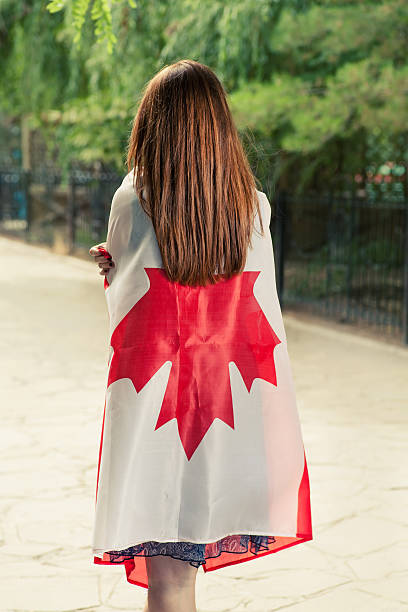 Backside view of young women wrapped around with Canada flag stock photo