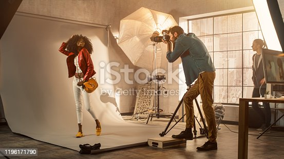Backstage of the Photo Shoot: Photographer Taking Photos of Beautiful Black Model with Professional Camera. Fashion Magazine Studio Photoshoot. Golden Hour Shot.