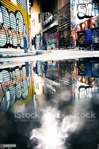 Graffiti covered ghetto streets reflected in puddle.