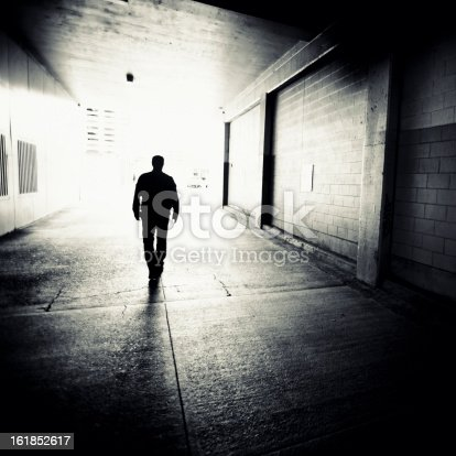 man walking through downtown alley into the light.
