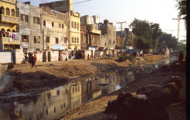 backstreets along a canal in the old city section of lahore pakistan - pakistano foto e immagini stock