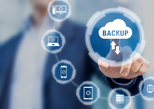 istock Backup files and data on internet with cloud storage technology that sync all online devices and computers with network connection, protection against loss, business person touch screen icon concept 1162629915