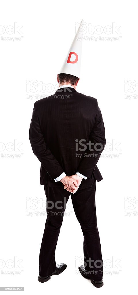 Backview embarrassed ashamed businessman wearing dunce cap standing in corner stock photo