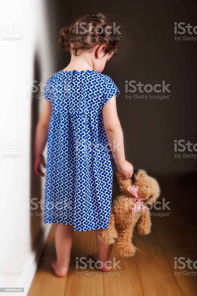 Backview little girl holding teddy bear stock photo
