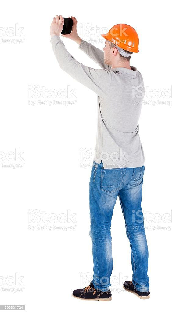 Backview of an engineer in construction helmet stands and enjoys stock photo
