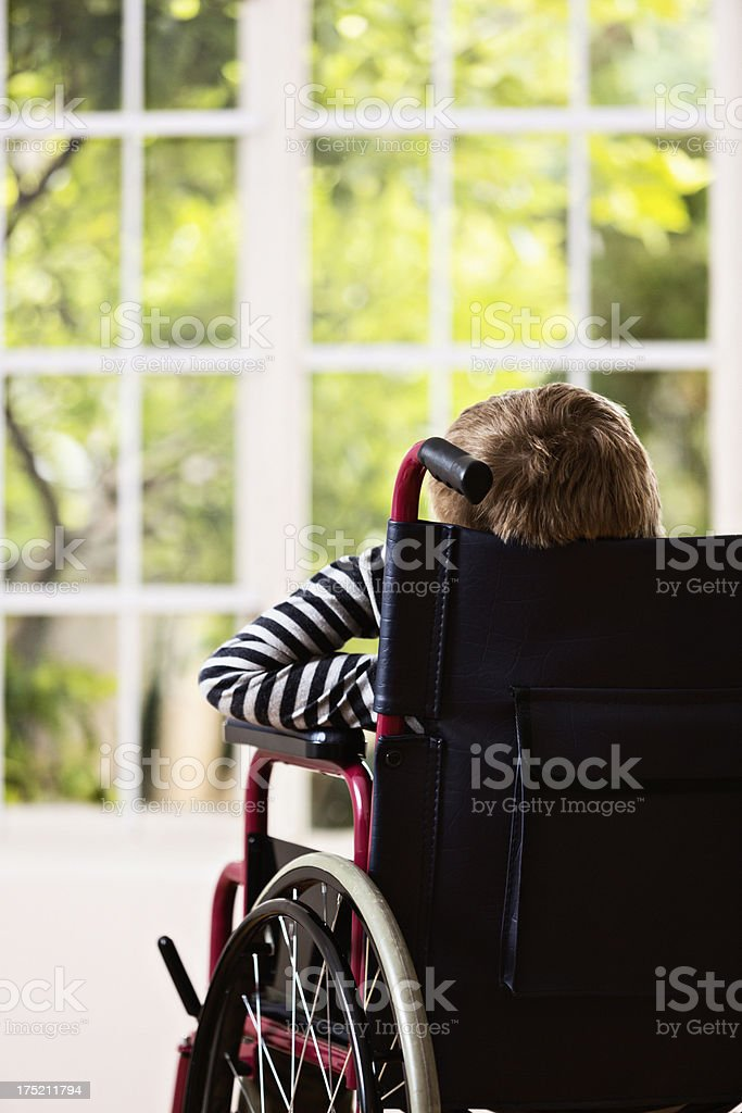 Backview of boy in wheelchair looking longingly through window stock photo